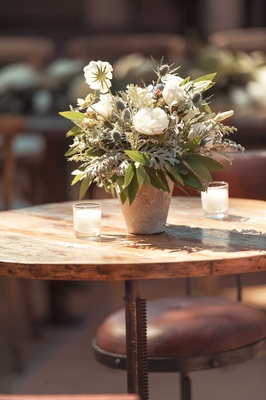 Rustic round wood cocktail table outdoor wedding reception candles white flower greenery centerpiece