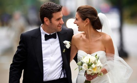 Bride in strapless Monique Lhuillier wedding dress with ivory bouquet and groom in tuxedo