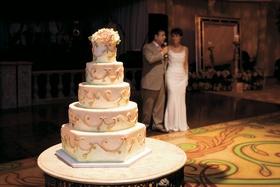 Wedding cake with golden swirls and light green beading