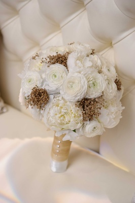 white bridal bouquet with gold spray painted baby's breath white ranunculus white peony flowers