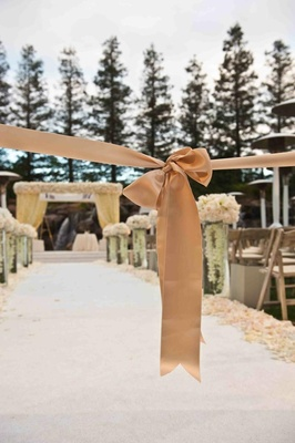 Petal-lined white aisle with wood chairs and flowers