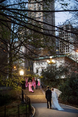 Bride and groom walk up steps to NYC hotel from Central Park