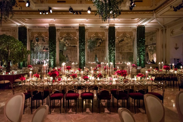 wedding reception gold chairs burgundy green hedge walls mirror trees as centerpieces red flowers
