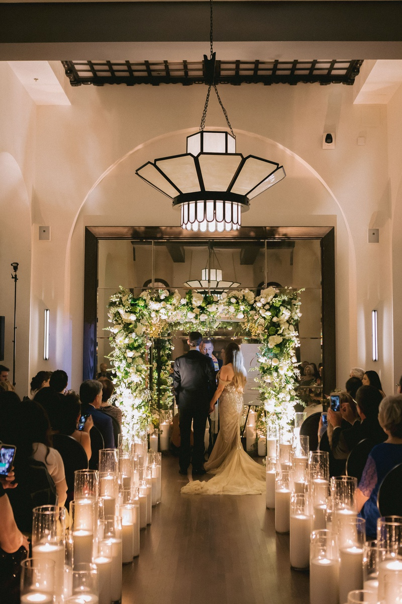 wedding ceremony hotel figueroa candles lining aisle greenery white flower chuppah