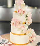 four layer wedding cake with gold border and fresh flowers pink garden roses cascading down from top