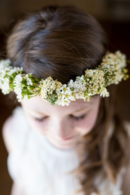 Flower girl wearing flower crown with green white yellow flowers halo brown hair