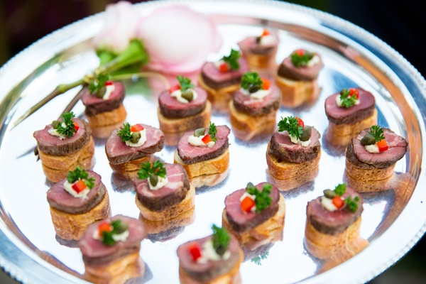 Bread crostini with mini steak and garnish on platter