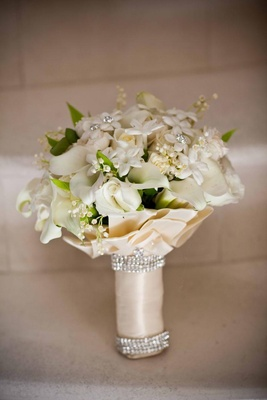 White and ivory flowers wrapped in champagne ribbon