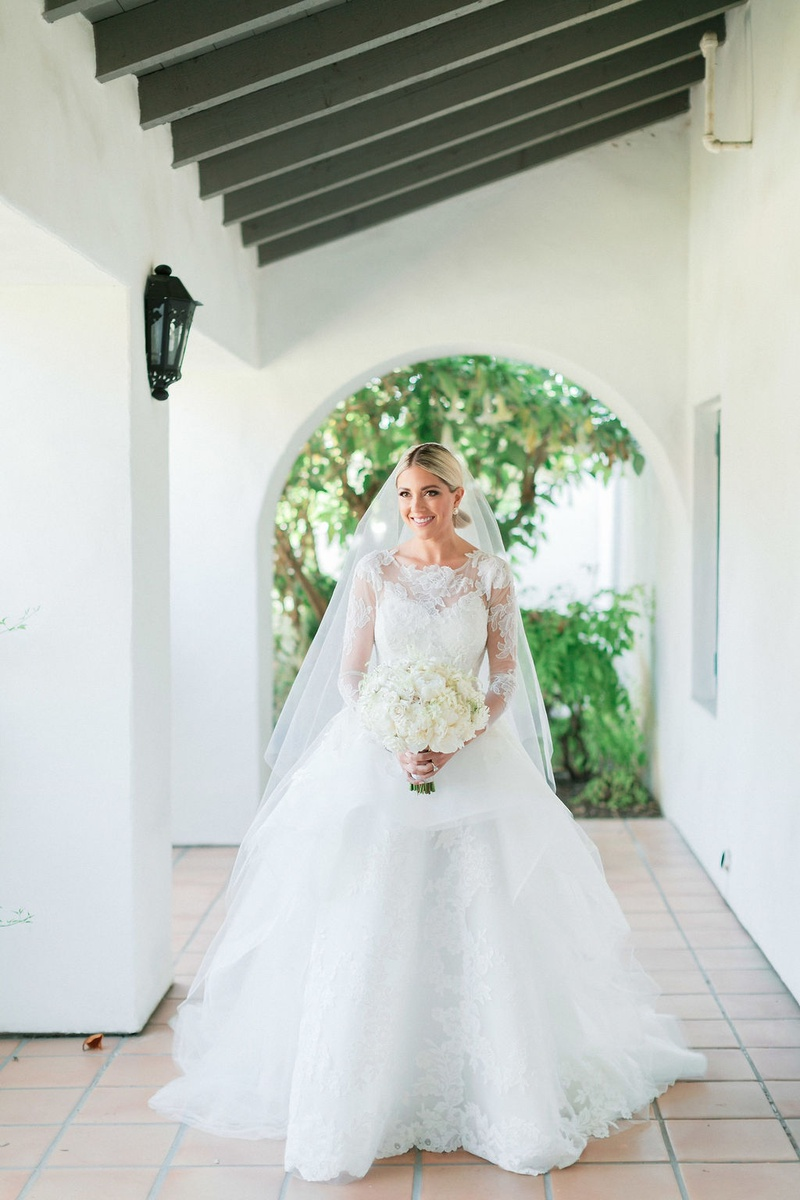 bride in long-sleeve lace Carolina Herrera ball gown with veil and ivory bouquet