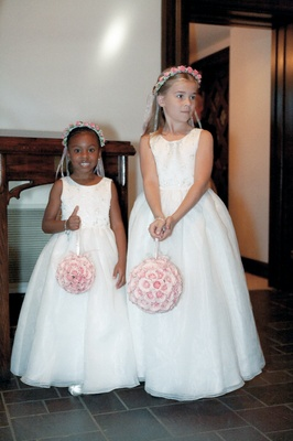 flower girls wearing white dresses wearing pink flower crowns and pink flower purses