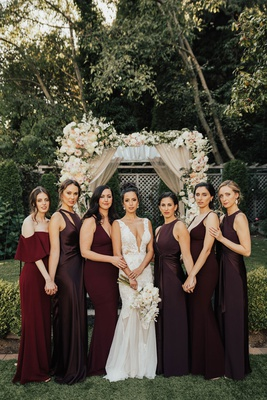 bride in low plunging neckline gown hair up with bridesmaids in mismatch burgundy oxblood dresses