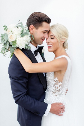 bride in francesca miranda wedding dress with butterfly appliques, groom in navy tux
