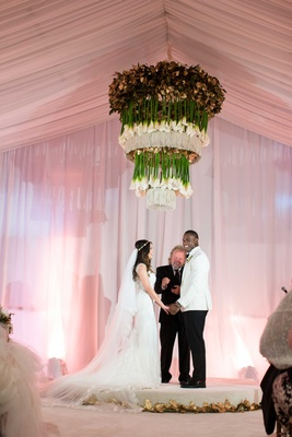 Heidi and DeMarco exchanging vows below the chandelier at their wedding