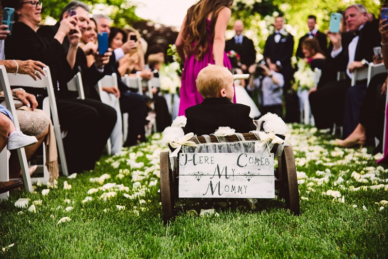 Bridesmaid pulling little ring bearer bride son in wagon with here comes my mommy sign wedding ideas