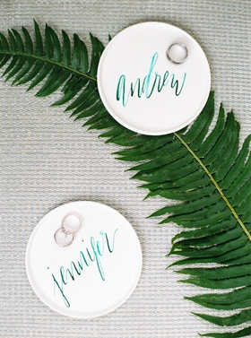 Wedding rings on personalized teal modern calligraphy on ring holder trays white on fern leaf