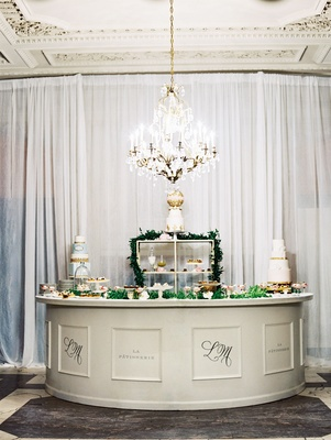 Wedding reception indoor dessert station with cakes and French pastries Paris inspired wedding