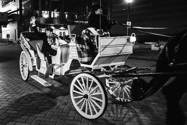 black and white photo of bride and groom in horse-drawn carriage leaving wedding