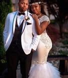 bride in form fitting mermaid wedding dress with sheer details headband groom in white tuxedo jacket