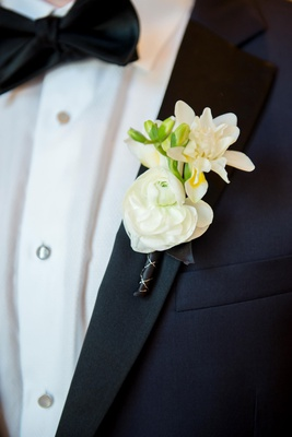 mixed floral boutonniere with white blossoms, ranunculus and tropical anthurium hybrid