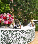 wedding reception backyard wedding curved white bar with greenery pink flowers cocktail hour