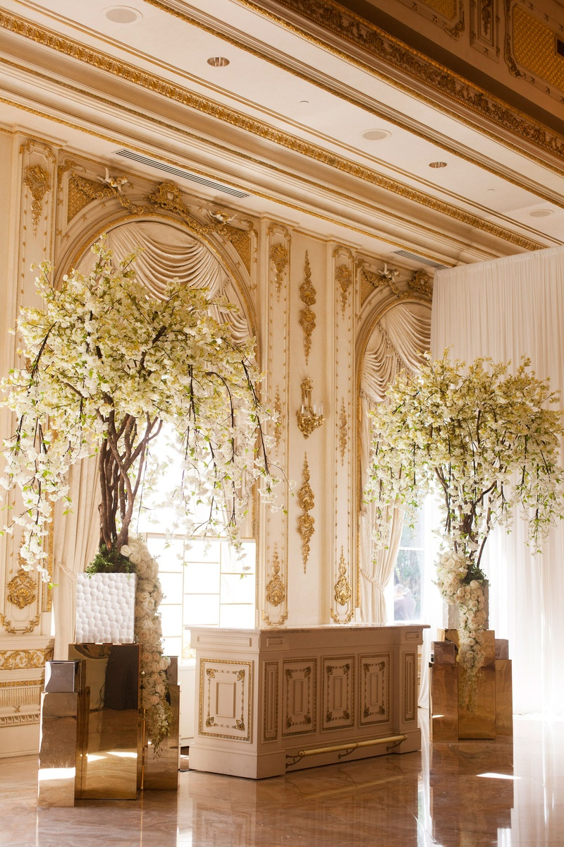 White flowers on tall tree by wedding bar white and gold bars