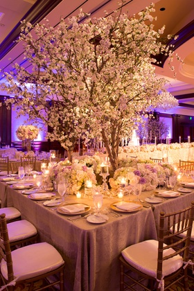 Balloom wedding reception table with cherry blossom tree surrounded by white, purple roses, green