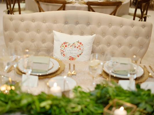 Wedding reception decor rustic wedding green garland gold place setting heart pillow on settee