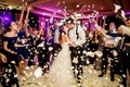 wedding reception bride and groom kiss guests tossing white rose flower petals purple pink lighting