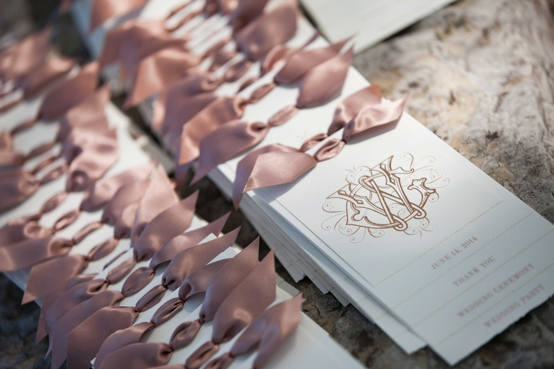 delicate white programs with gold calligraphy and pink bows