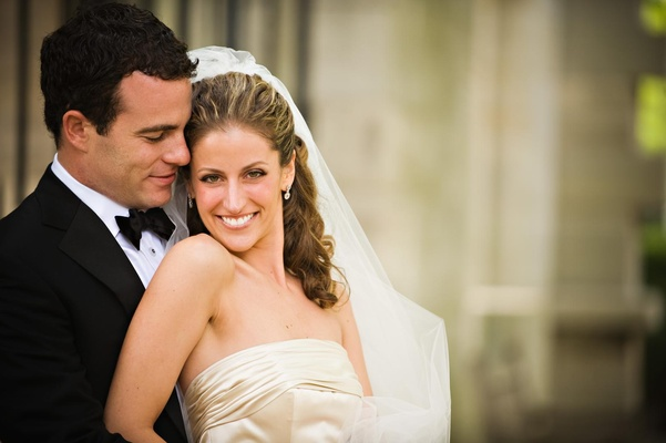 Bride in a strapless Monique Lhuillier gown and veil with groom in tuxedo
