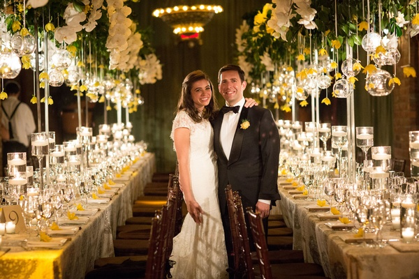 Bride in lace cap sleeve wedding dress Mark Ingram Atelier in reception room yellow decorations