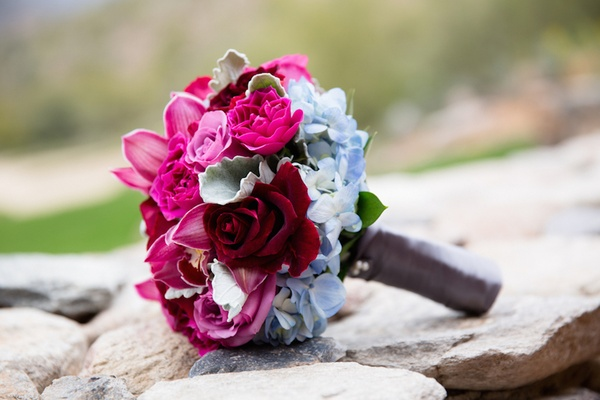 Bridesmaid bouquet with light blue hydrangea, pink rose, red rose, and burgundy orchid