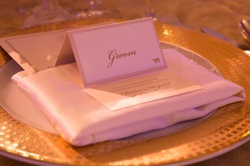 Wedding reception place setting with groom's place card, donation wedding favor card, white napkin