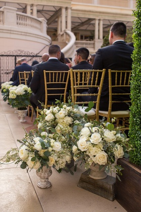 ceremony on patio of the bellagio, flower arrangements in stone vases at base of aisle