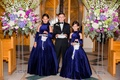 Wedding at church purple flower arrangements flower girls in royal blue ball gowns ring bearer