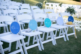 names of guests placed on white chairs at beach wedding