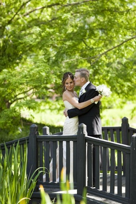 Groom in a black tuxedo kisses bride