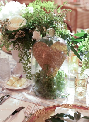 Reception table with glitter heart in glass jar with greenery