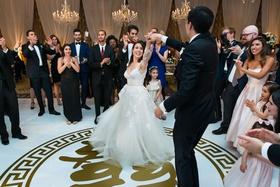 bride in monique lhuillier wedding dress groom in tuxedo dancing on custom dance floor gold emblem