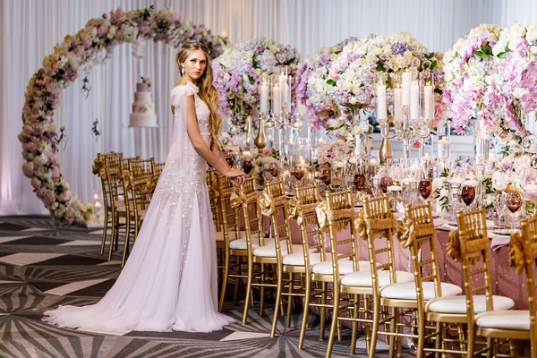 Wedding reception gold chairs purple pink white centerpieces candles bride in long dress godet skirt