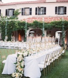 long reception tables white linens gold candelabra cascading floral runner gold chairs