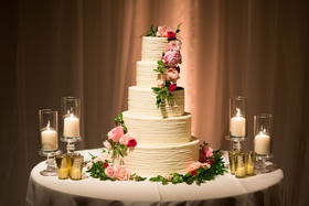 Wedding cake with five ivory layer tier with candles pink flowers green leaves greenery