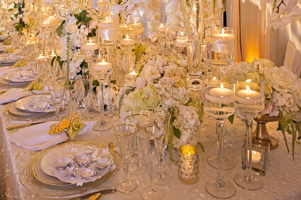 white roses and orchids, glass stands for floating candles, textured linens