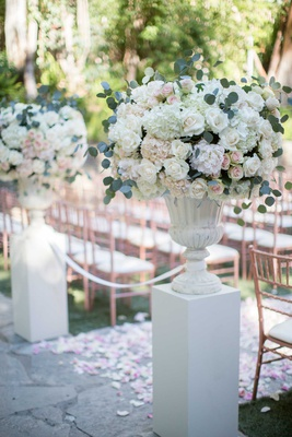 two white pillars with lush floral arrangements and eucalyptus leaves framing start of aisle