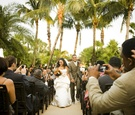African American bride and groom walk up aisle guests take photos