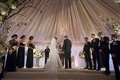 Tented wedding ceremony with a draped blush and ivory ceiling