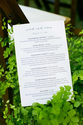 a couples ceremony program for tradition jewish wedding sitting amongst green foliage