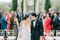 Bride and groom smile at each other during outdoor wedding ceremony guests look at couple chairs