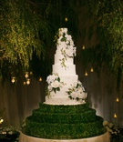 wedding cake white with flowers and greenery hedge boxwood trees candle lights forest