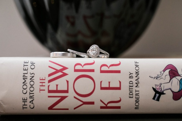 The New Yorker book with wedding band, eternity band, and engagement ring on top
